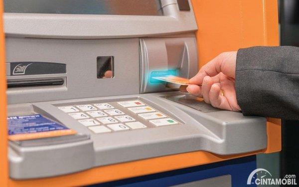 tangan yang sedang membayar pajak melalui ATM