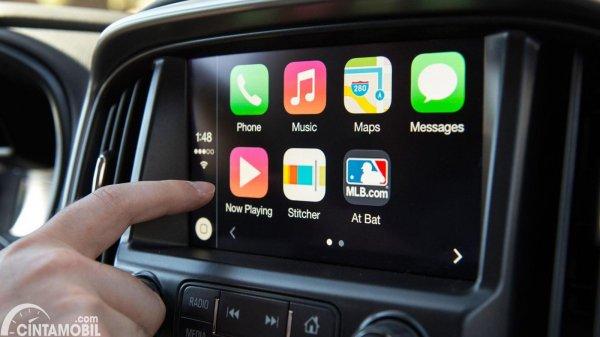 tangan yang menekan Android Auto pada mobil