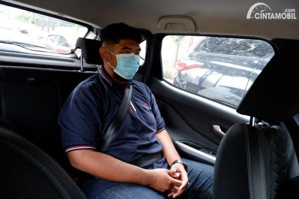 Foto tester tim Cintamobil.com sedang duduk di kursi belakang Nissan Magnite