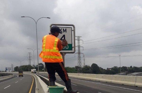 Foto seorang petugas sedang membersihkan rambu-rambu jalan Tol BORR