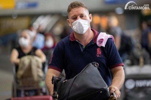 pengunjung yang sedang menggunakan masker di bandara