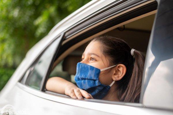 anak perempuan memakai masker di mobil