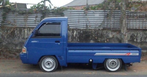 Gambar sebuah mobil pick up berwarna biru dilihat dari sisi depan