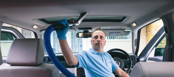 Membersihkan plafon mobil dengan vacuum cleaner
