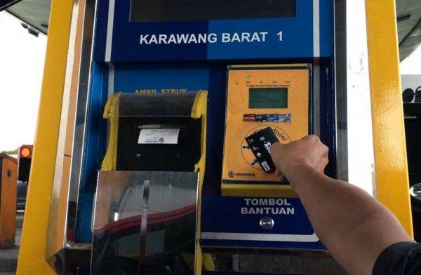 Foto pengendara melakukan pembayaran tol dengan uang elektronik