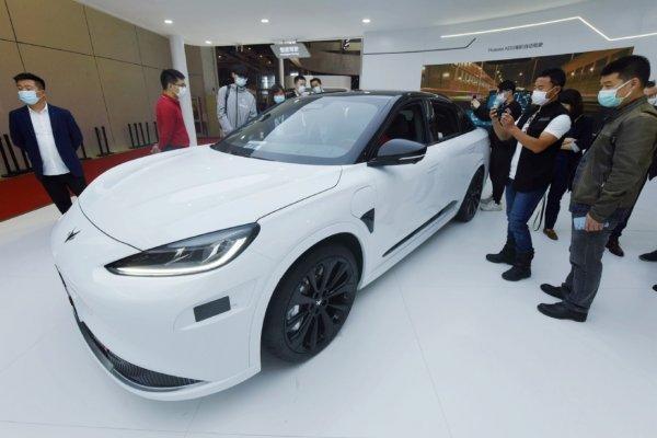 Foto menunjukkan para pengunjung melihat model Tesla yang dipamerkan