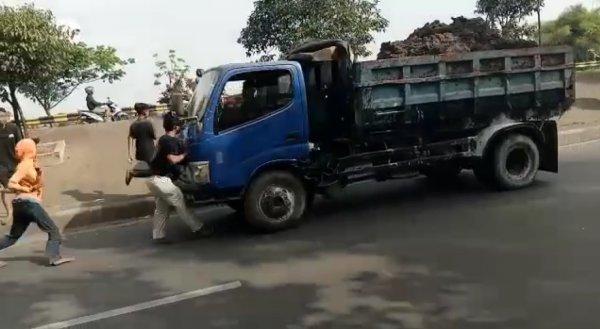 Foto menunjukkan remaja mencegat truk tertabrak