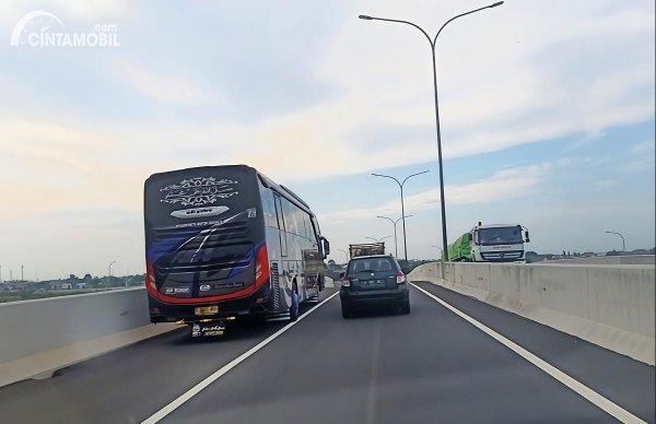 Foto menunjukkan bus menyalip melalui bahu jalan di jalan Tol Semarang-Batang